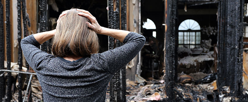 woman standing in front of house destroyed by fire